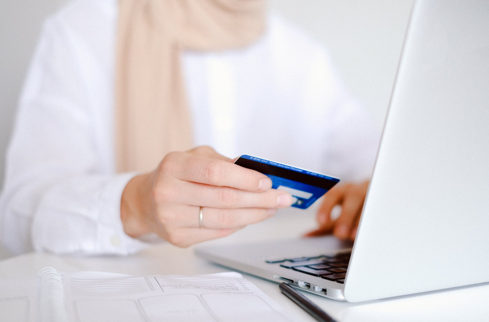 Faceless person holds a credit card with a laptop