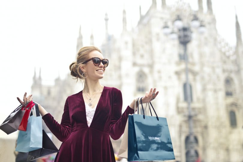woman-wearing-maroon-velvet-plunge-neck-long-sleeved-dress-while-carrying-several-paper-bags