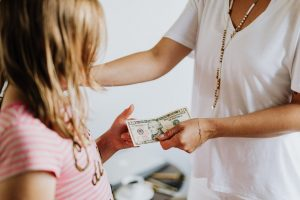 a Parent handing a dollar bill to his child