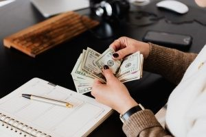 a woman counting money for storage expenses, a notebook, and a pen