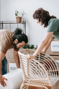 a man and a woman packing items for storage in labeled boxes