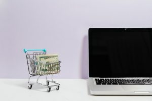 macbook-pro-on-white-table-beside-a-miniature-shopping-cart-with-money