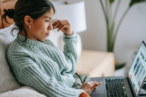 focused-young-ethnic-woman-with-credit-card-and-laptop